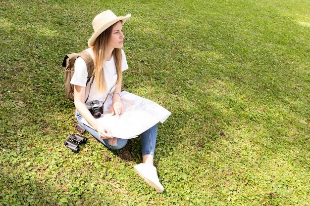 Frau mit dem hut, der auf gras sitzt und weg schaut