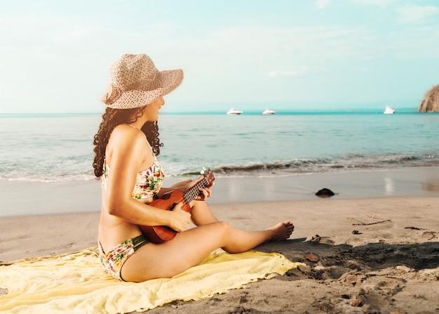 Frau mit dem hut, der ukulele auf sandigem strand spielt