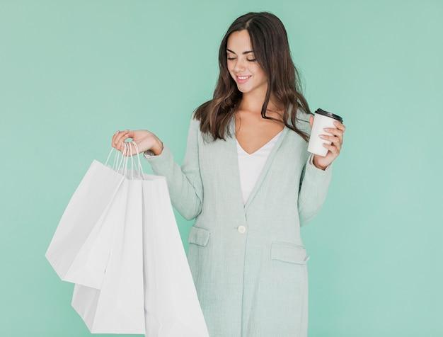 Frau mit dem kaffee, der die einkaufsnetze betrachtet