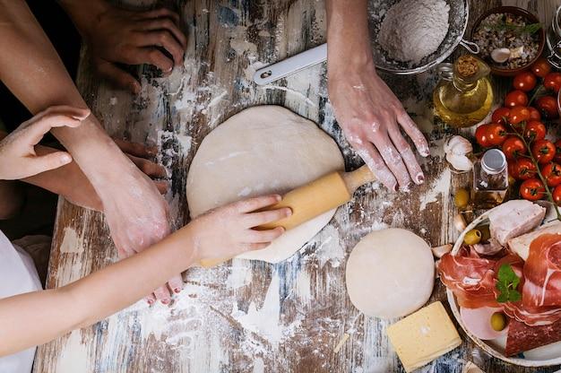 Frau mit dem kind, das teig für selbst gemachte pizza zubereitet. leichtes tonen draufsicht