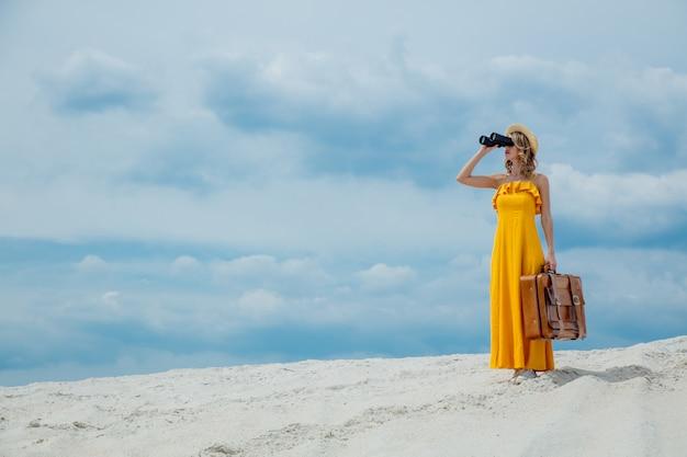 Frau mit dem koffer, der in den ferngläsern schaut