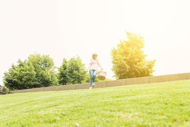 Frau mit dem korb, der im park aufweckt