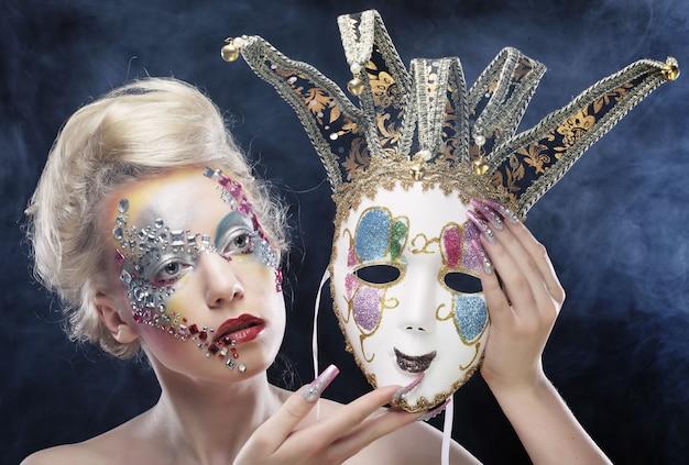 Frau mit dem künstlerischen make-up, das maske hält