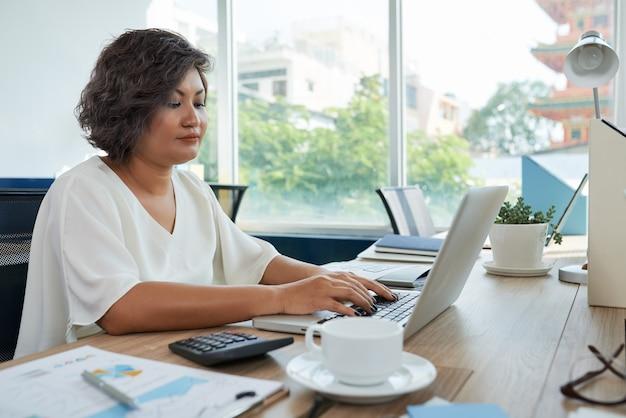 Frau mit dem kurzen gewellten haar, das am schreibtisch im büro sitzt und an laptop arbeitet
