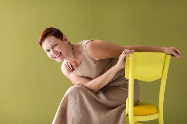 Frau mit dem kurzen haar, das auf stuhl sitzt
