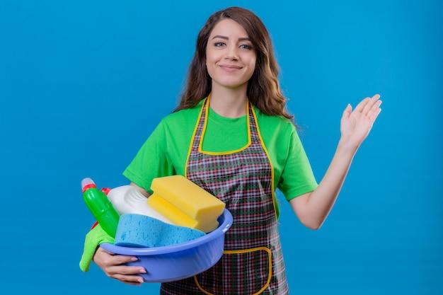 Frau mit dem langen gewellten haar, das schürze und gummihandschuhe trägt, die becken mit reinigungsgebühr halten, lächelnd winkend mit hand stehend auf blau