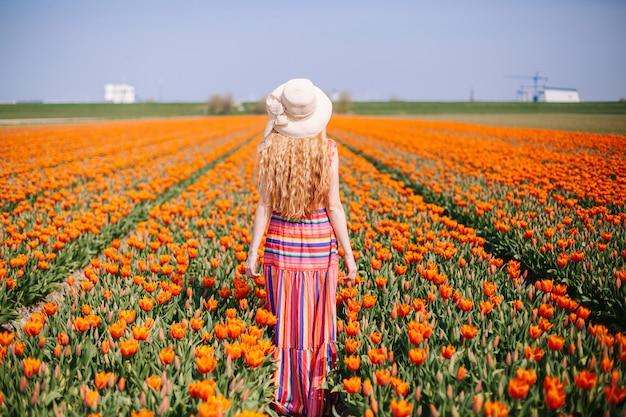 Frau mit dem langen roten haar, das ein gestreiftes kleid bereitsteht die rückseite auf buntem tulpenfeld trägt.