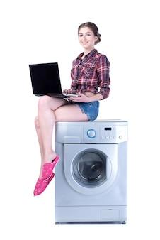 Frau mit dem laptop, der auf der waschmaschine sitzt.