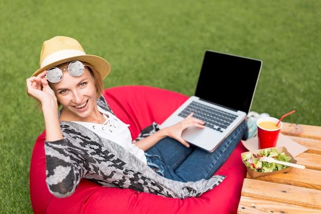 Frau mit dem laptop, der kamera betrachtet