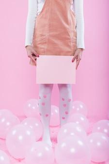 Frau mit dem leeren papier, das auf boden mit ballonen steht
