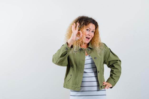 Frau mit dem lockigen blonden haar, das ok geste in der grünen jacke zeigt und erfreut, vorderansicht schaut.