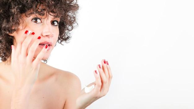 Frau mit dem lockigen haar, das creme an ihrem gesicht gegen weißen hintergrund aufträgt