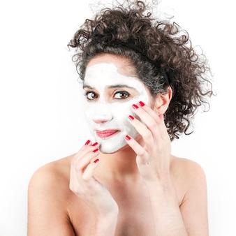 Frau mit dem lockigen haar, das gesichtscreme auf ihrem gesicht gegen weißen hintergrund aufträgt