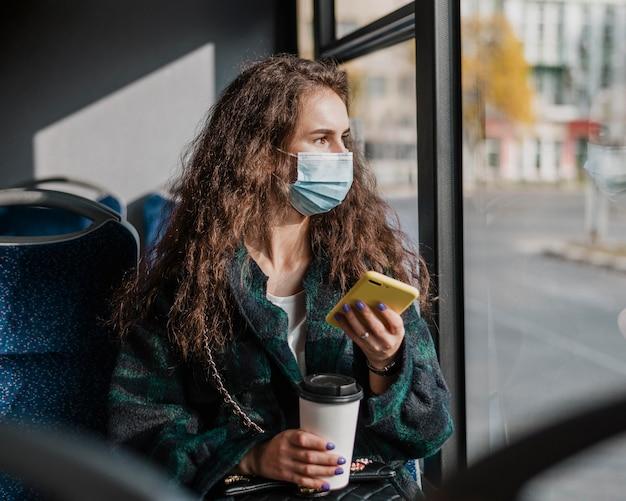 Frau mit dem lockigen haar, das handy und kaffee hält