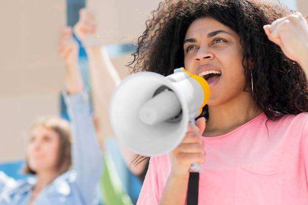 Frau mit dem lockigen haar, das niedrige ansicht protestiert