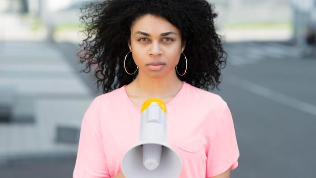 Frau mit dem lockigen haar, das vorderansicht protestiert
