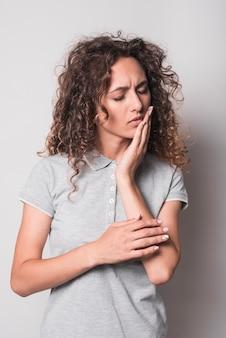 Frau mit dem lockigen haar, das zahnschmerzen gegen grauen hintergrund hat