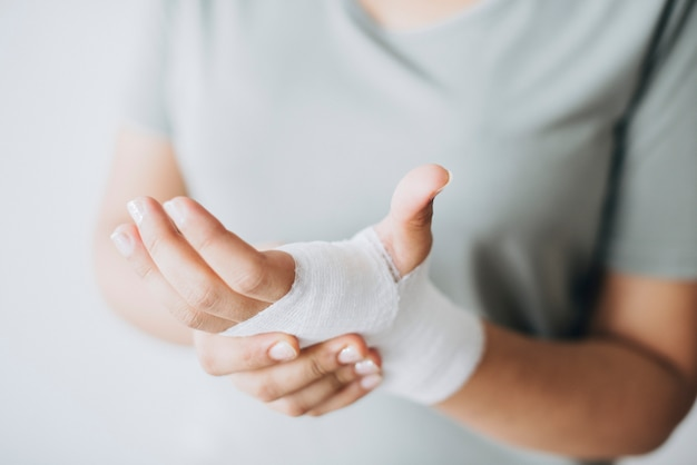 Frau mit dem mullverband um ihre hand gewickelt