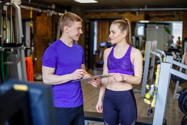 Frau mit dem persönlichen trainer, der trainingsplan in der turnhalle vorbereitet.