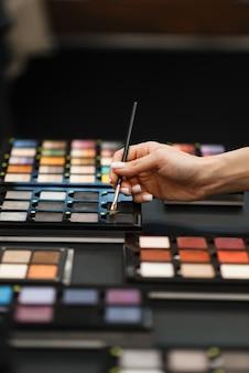 Frau mit dem pinsel, der lidschattenton im kosmetikgeschäft wählt. käufer im luxus-schönheitssalon, kundin im modemarkt