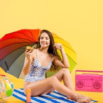 Frau mit dem regenschirm, der auf strandmatte sitzt und kokosnussgetränk genießt
