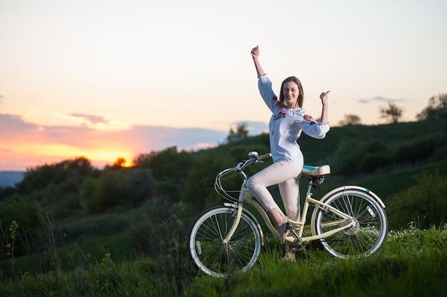 Frau mit dem retro- fahrrad, das am hügel steht und sich daumen bei sonnenuntergang zeigt