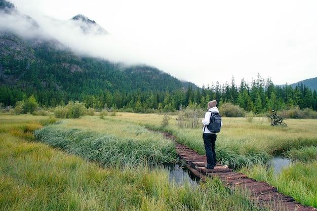 Frau mit dem rucksack, der in forest mountains wandert.