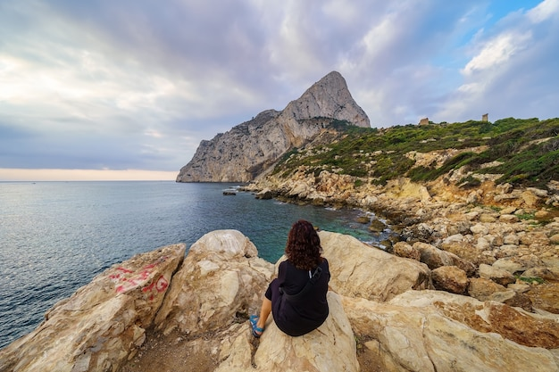 Frau mit dem rücken, die auf einigen felsen sitzt und den sonnenaufgang über dem horizont des meeres beobachtet