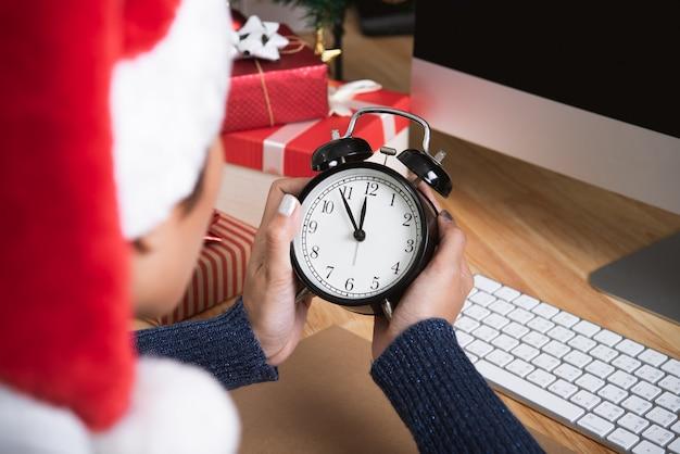 Frau mit dem sankt-hut, der uhr auf schreibtischbüro nach weihnachtsfeier und guten rutsch ins neue jahr hält.