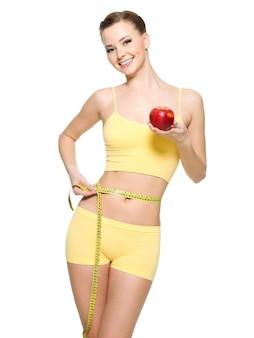 Frau mit dem schönen schlanken sportlichen körper, der die wistline misst und frischen roten apfel hält. porträt isoliert auf weiß