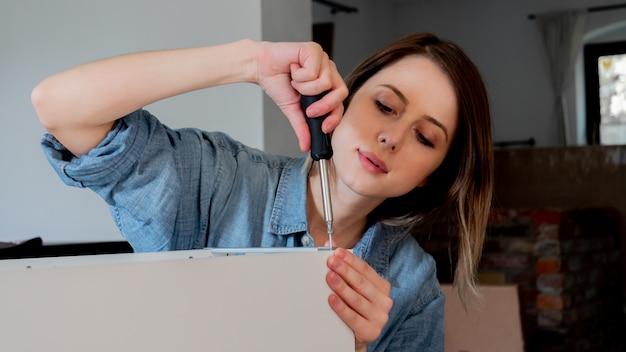 Frau mit dem schraubenzieher, der zu hause möbel persönlich installiert