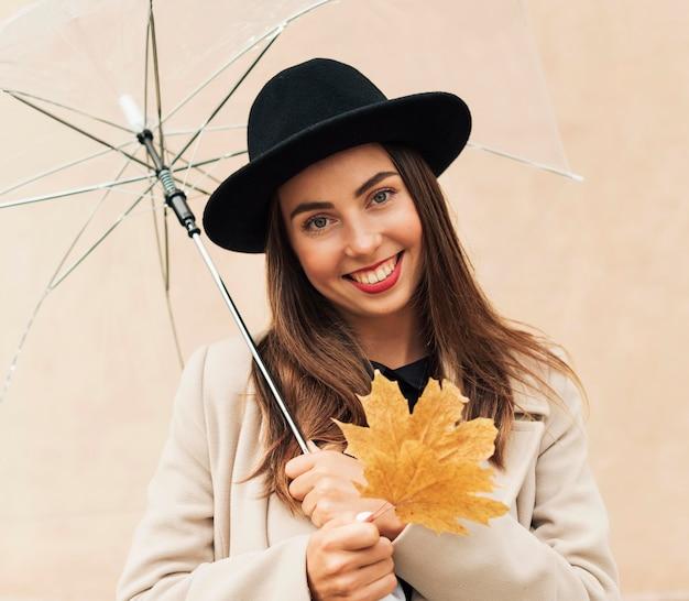 Frau mit dem schwarzen hut, der einen regenschirm hält