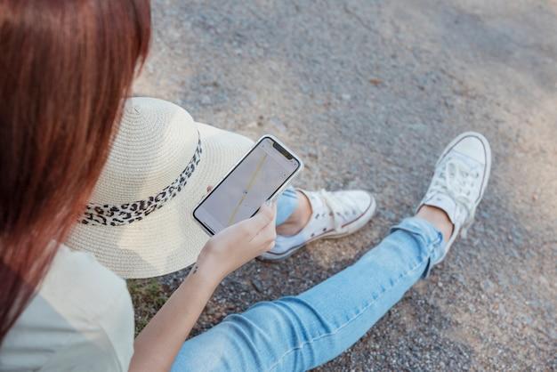 Frau mit dem smartphone, der an ihrem auto sich lehnt