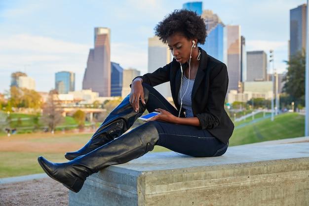 Frau mit dem smartphone, der im park sitzt