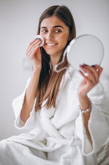 Frau mit dem spiegel, der make-up mit auflage entfernt