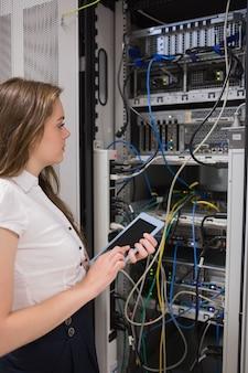 Frau mit dem tabletten-pc, der die server betrachtet