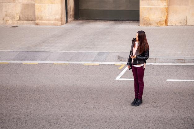 Frau mit dem telefon an der hand, die ein taxi wartet
