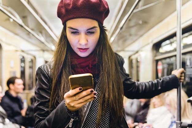 Frau mit dem telefon, das mit der metro in moskau reist