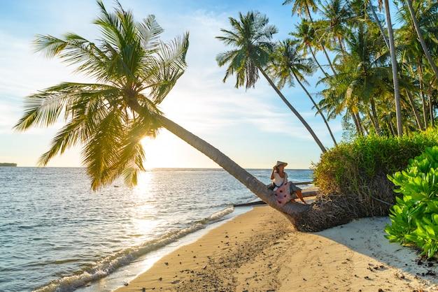 Frau mit dem traditionellen asiatischen hut, der auf dem tropischen strand sitzt auf kokosnusspalme sich entspannt