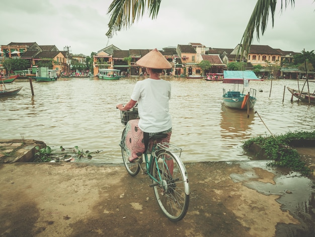 Frau mit dem traditionellen vietnamesischen hut, der auf die flussbank in hoi radfährt.
