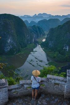 Frau mit dem traditionellen vietnamesischen hut, der die ansicht des tales betrachtet
