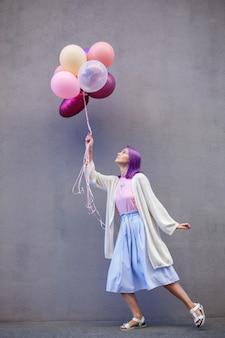 Frau mit dem violetten haar, das auf einem bein mit bündel luftballons steht
