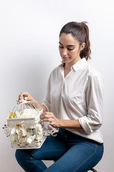 Frau mit dem vogelkäfig gefüllt mit blumen