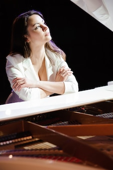 Frau mit dem weißen klavier auf der bühne.
