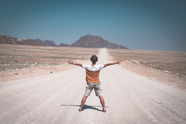 Frau mit den ausgestreckten armen, die auf der schotterstraße kreuzt die namibische wüste, im nationalpark namib naukluft, hauptreiseziel in namibia, afrika stehen. rückansicht, getönten bild.