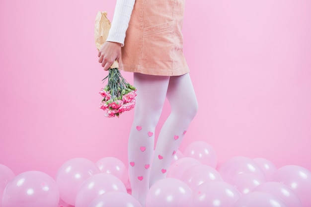 Frau mit den blumen, die auf boden mit ballonen stehen