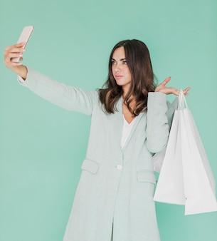 Frau mit den einkaufstaschen, die ein selfie nehmen