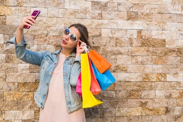 Frau mit den einkaufstaschen, die selfie nehmen