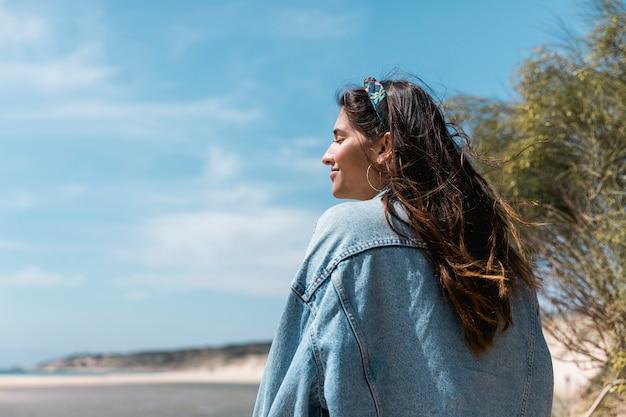 Frau mit den geschlossenen augen, die nahe tropischem strand sitzen