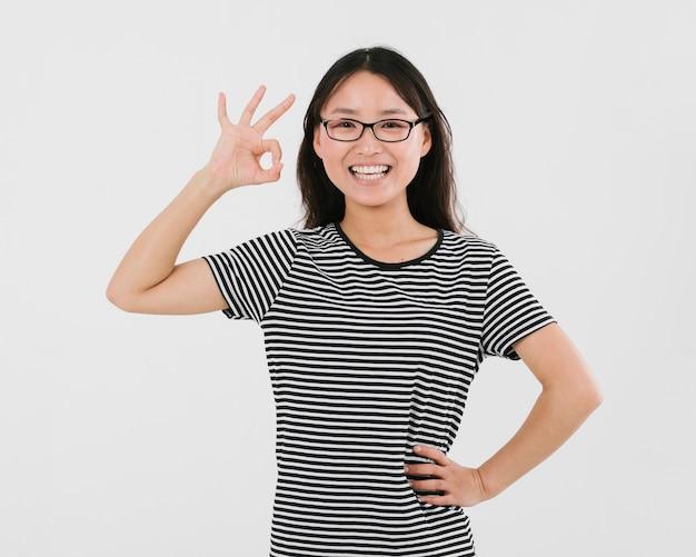 Frau mit den gläsern, die das okayzeichen geben